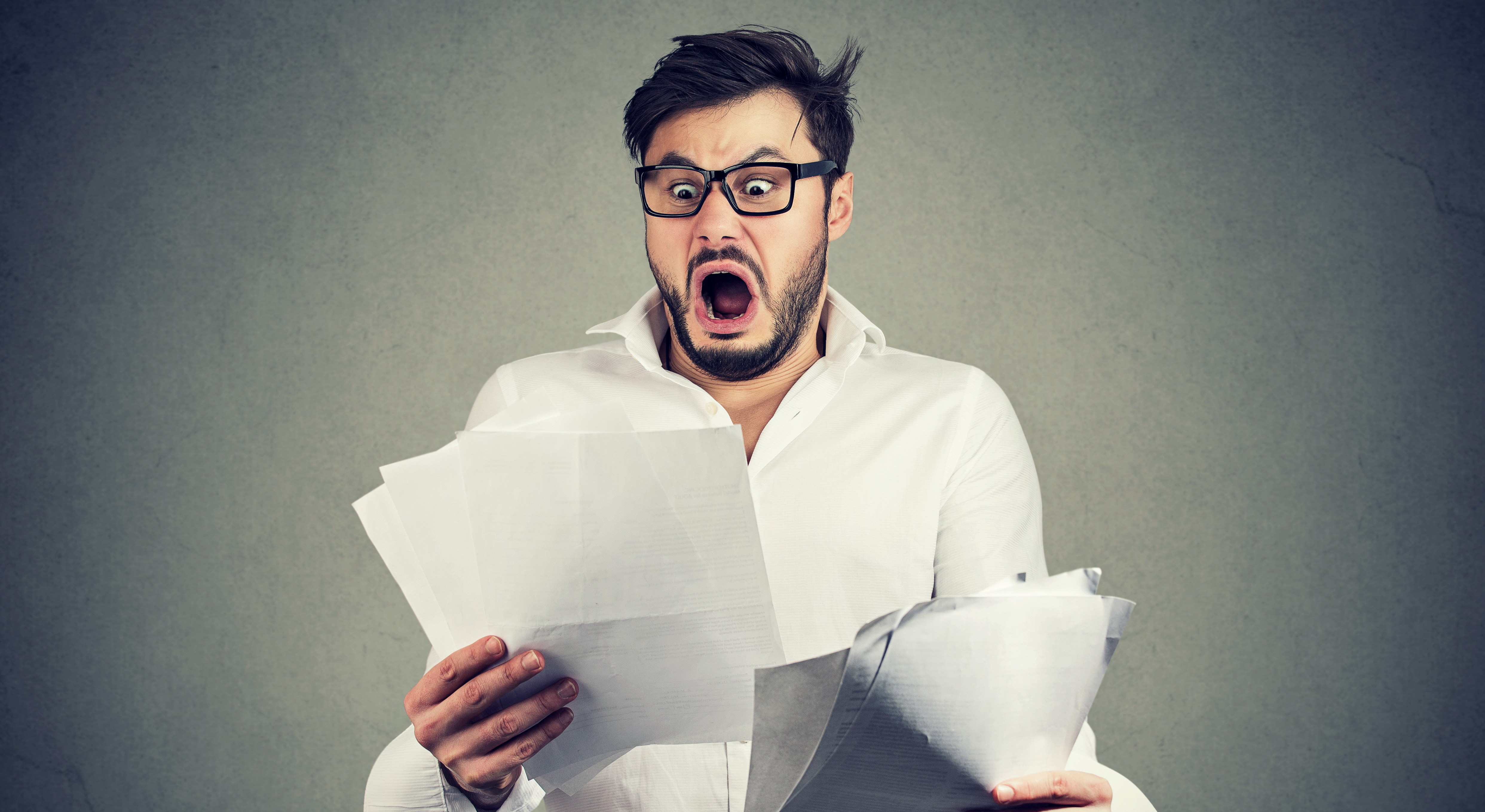 Shocked business man looking through papers with bills