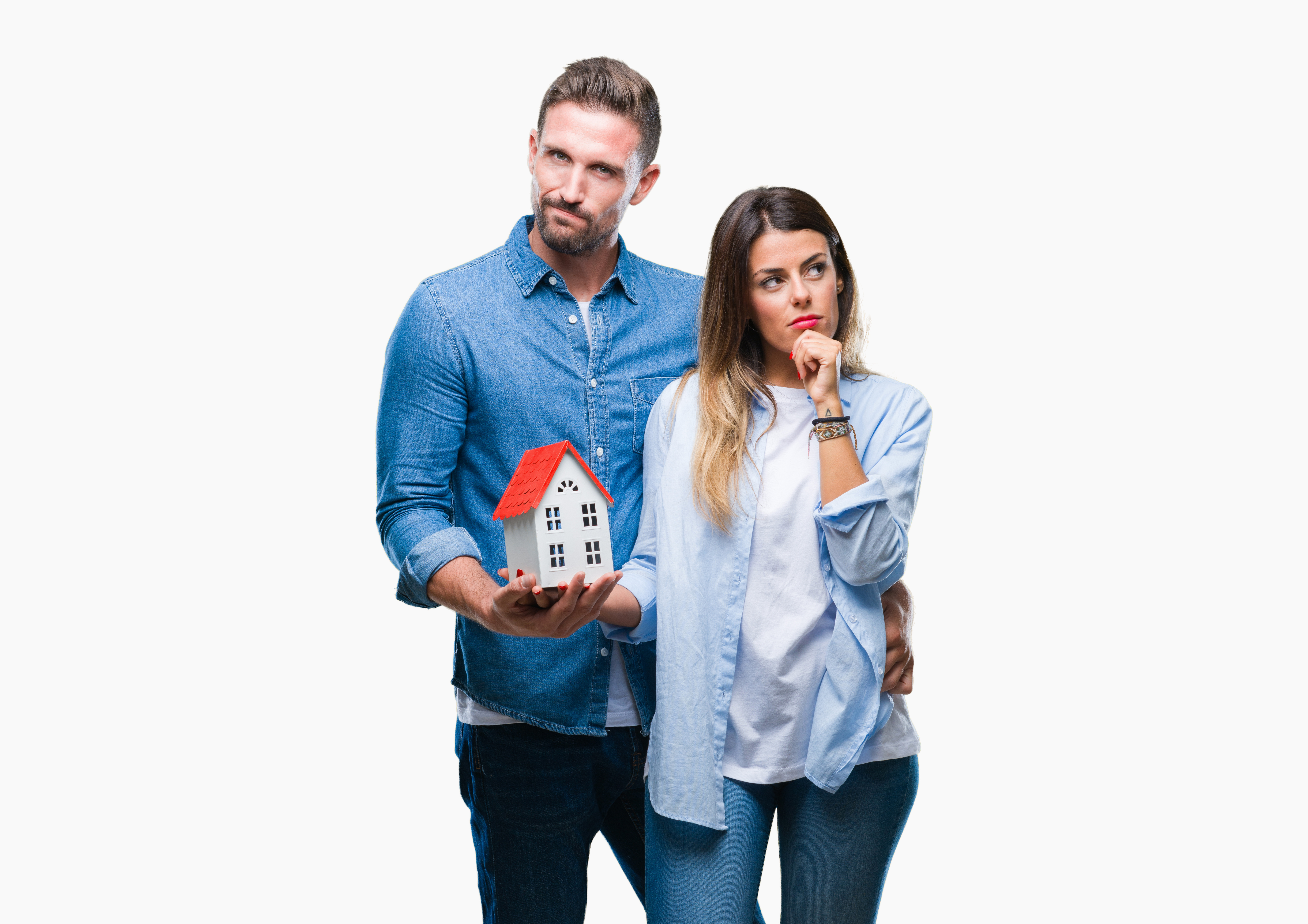 Young couple in love holding house over isolated background serious face thinking about question, very confused idea