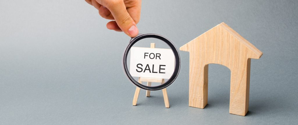 A miniature wooden house and a poster with the word For Sale